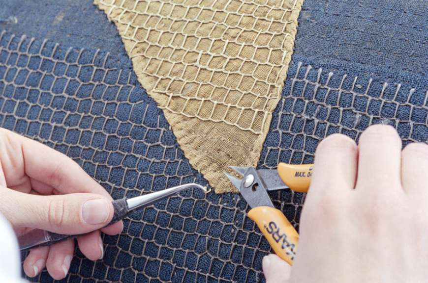 Removing the 1914 restoration stitches during the Star Spangled  Banner Flag's most recent conservation project